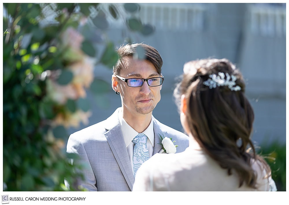 groom, wearing glasses and a gray tux, looking at his bride
