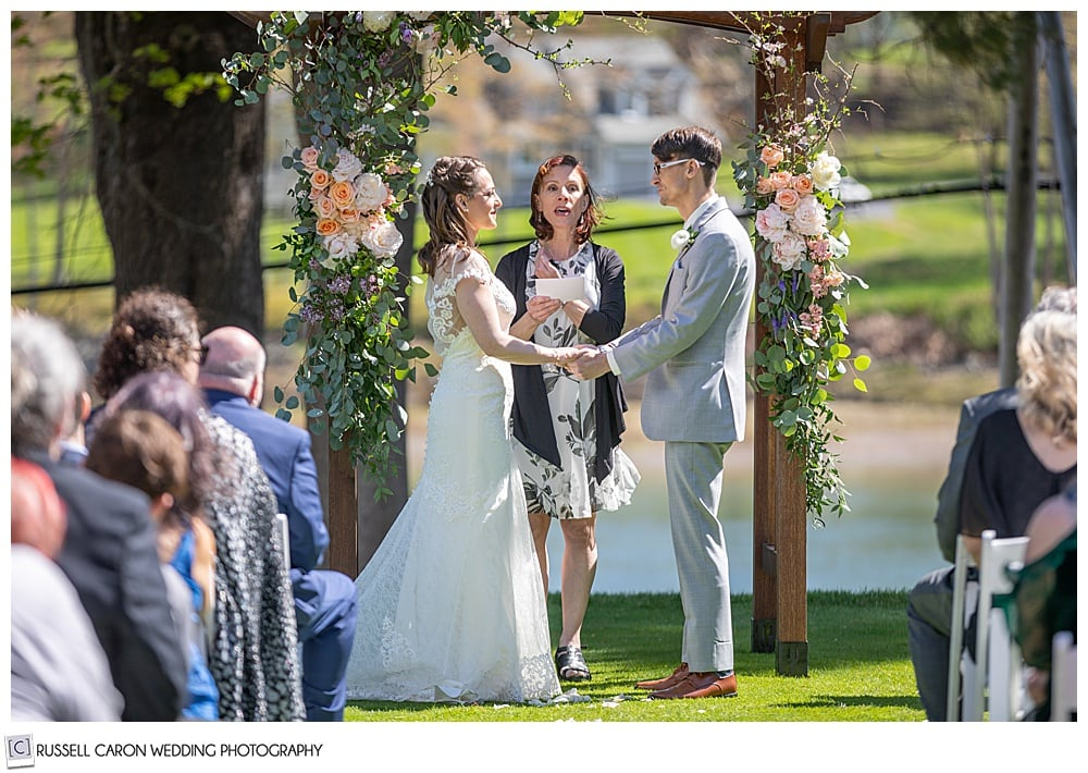 bride and groom standing in front of an officiant, at the outdoor ceremony site at York Golf and Tennis Club