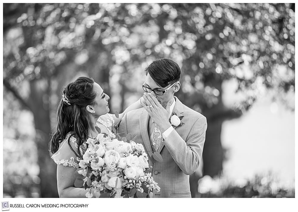 black and white photo of groom wiping his eyes as his bride looks on