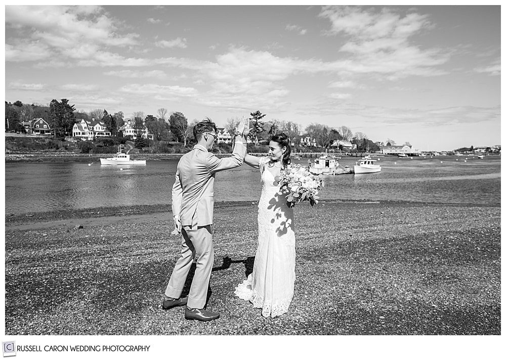 black and white photo of bride and groom giving each other a high five