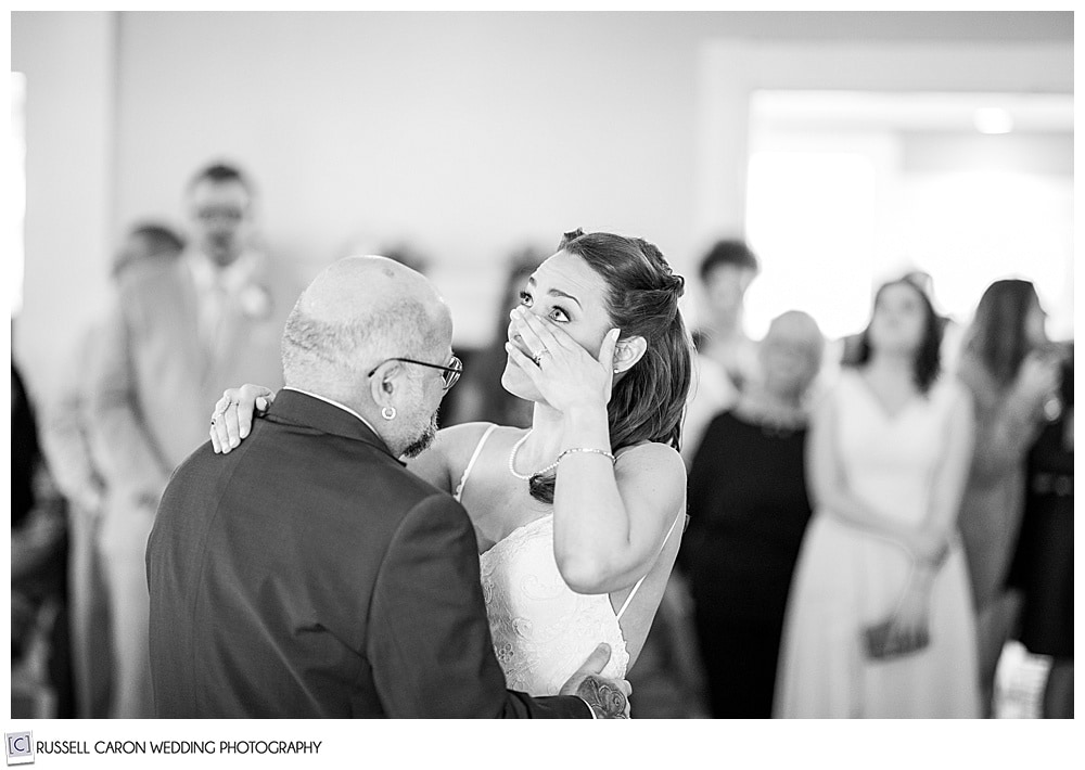 black and white photo of bride wiping her eye as she dances with her stepfather
