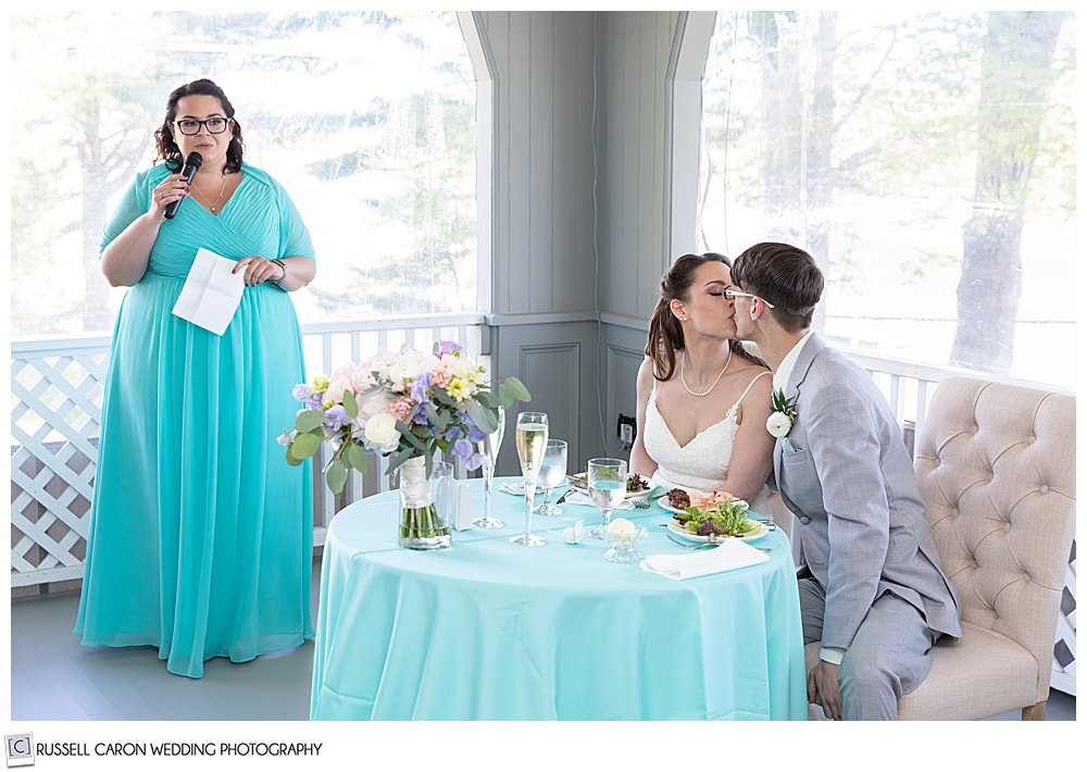 bride and groom kissing as maid of honor looks on