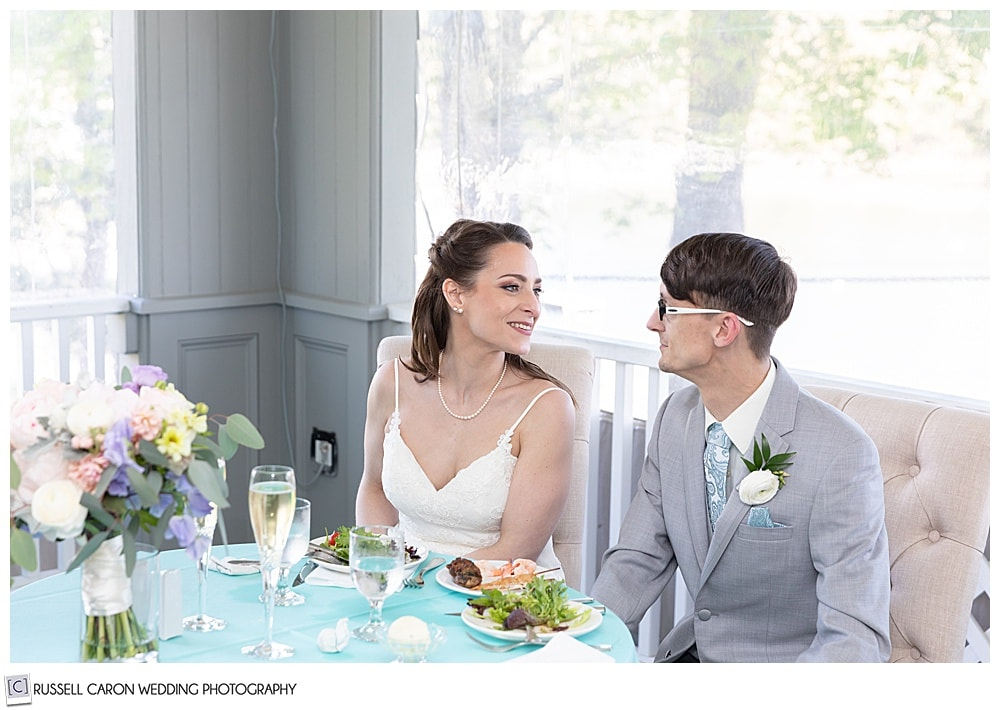 bride and groom looking at each other, while they sit at their sweetheart table