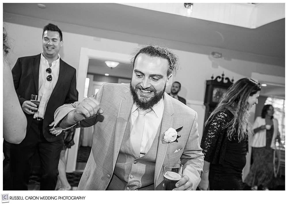 black and white photo of man dancing at a wedding reception