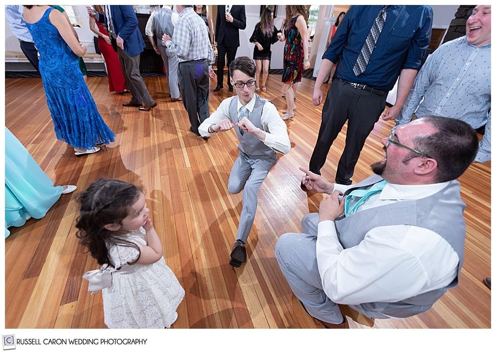 groom dancing with flower girl and groomsman