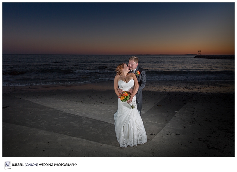 bride and groom on colony beach during sunset
