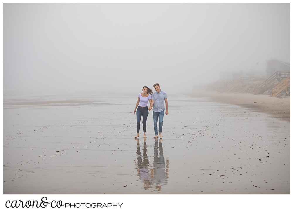 man and woman walking in the fog, on the beach, holding hands during a dreamy maine engagement session