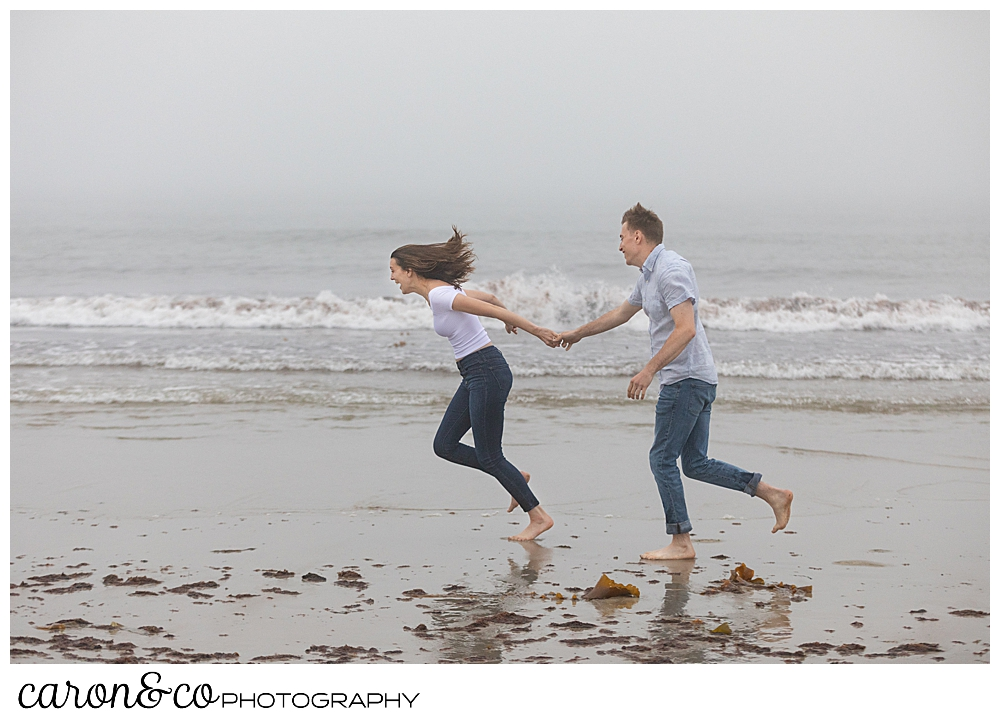 man and woman running along the shore at Biddeford Pool Beach, during a dreamy Maine engagement session