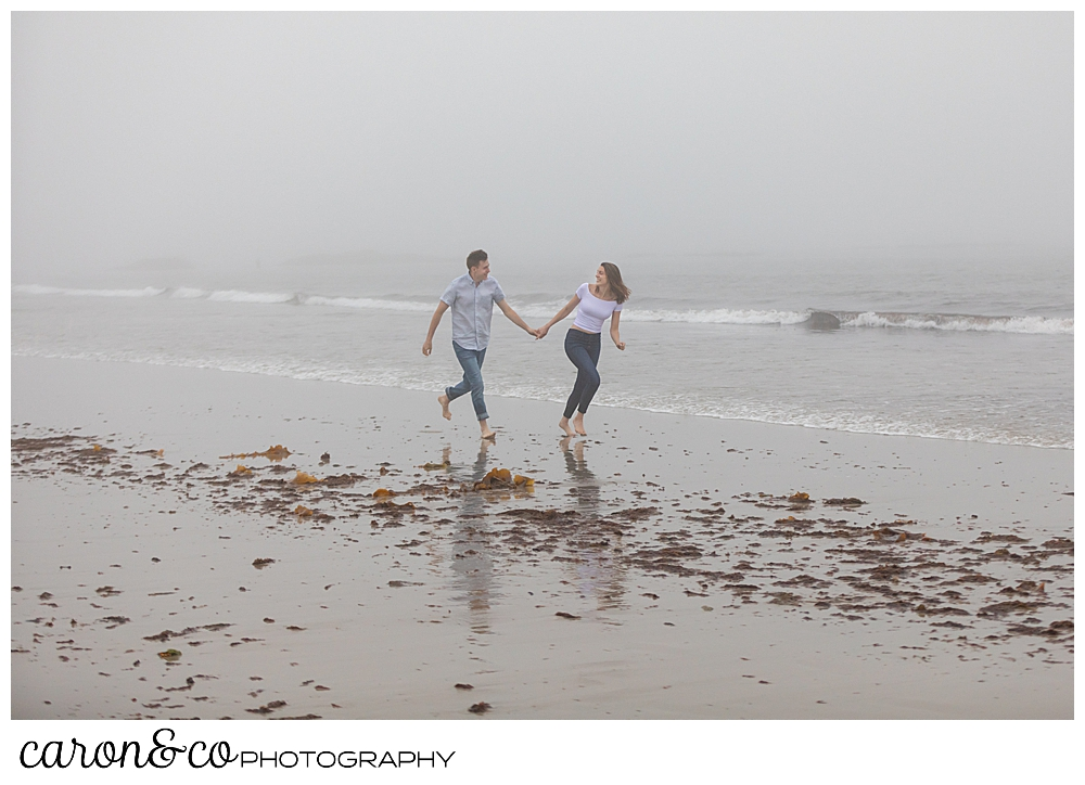 man and woman running in the fog at Biddeford Pool Beach, during a misty, dreamy maine engagement photo session