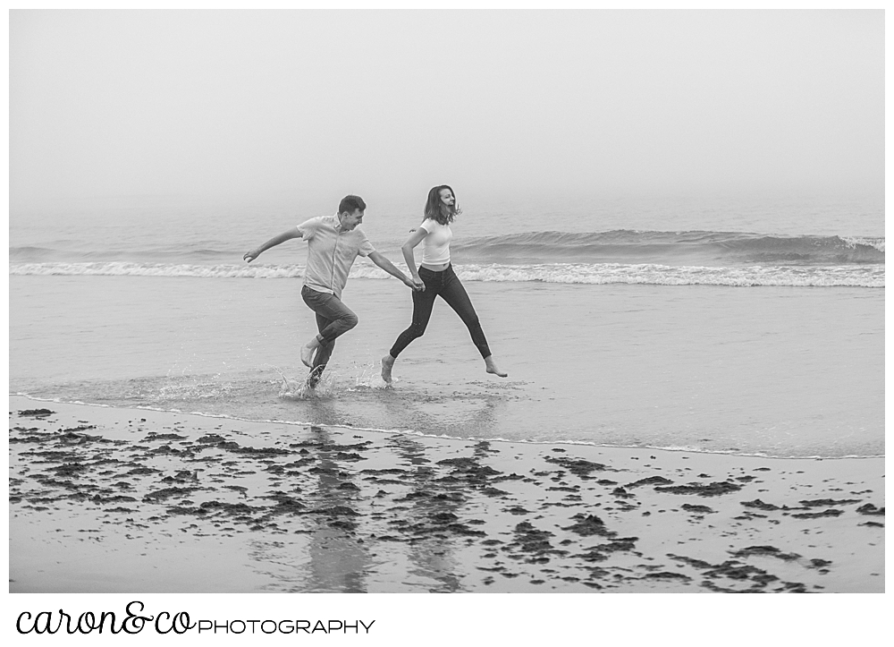 black and white photo of a man and woman running in the surf at Biddeford Pool Beach