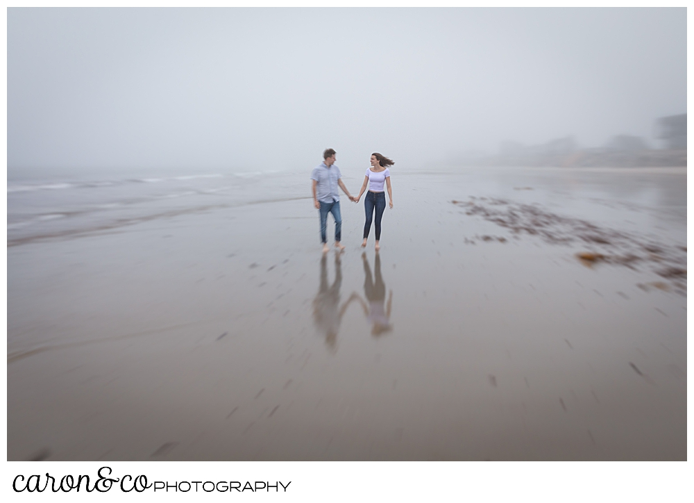 man and woman at Biddeford Pool beach, in the fog, holding hands and walking along the water