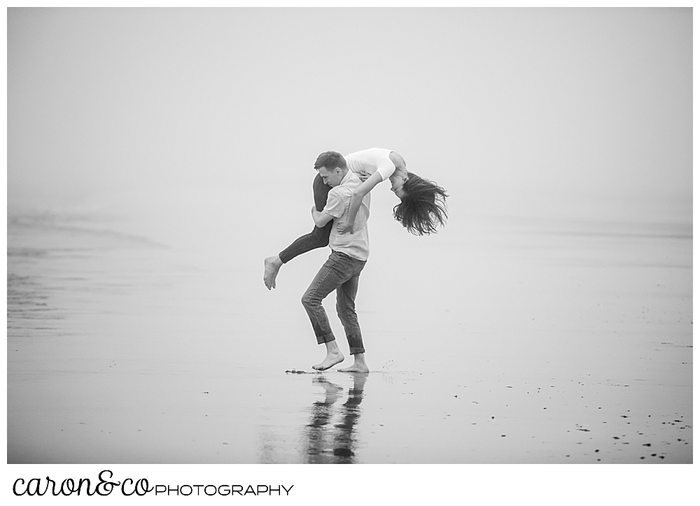 black and white photo of a man carrying a woman over his shoulder during a dreamy Maine engagement photo session