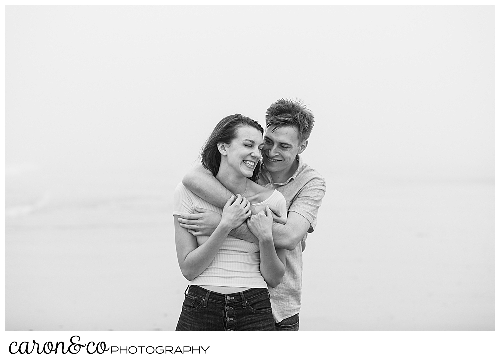black and white photo of a man and woman hugging each other