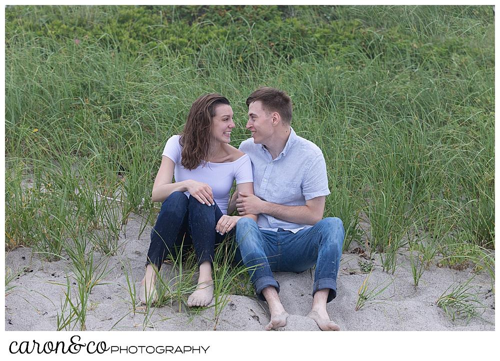 man and woman sitting near the dunes at Biddeford Pool Beach