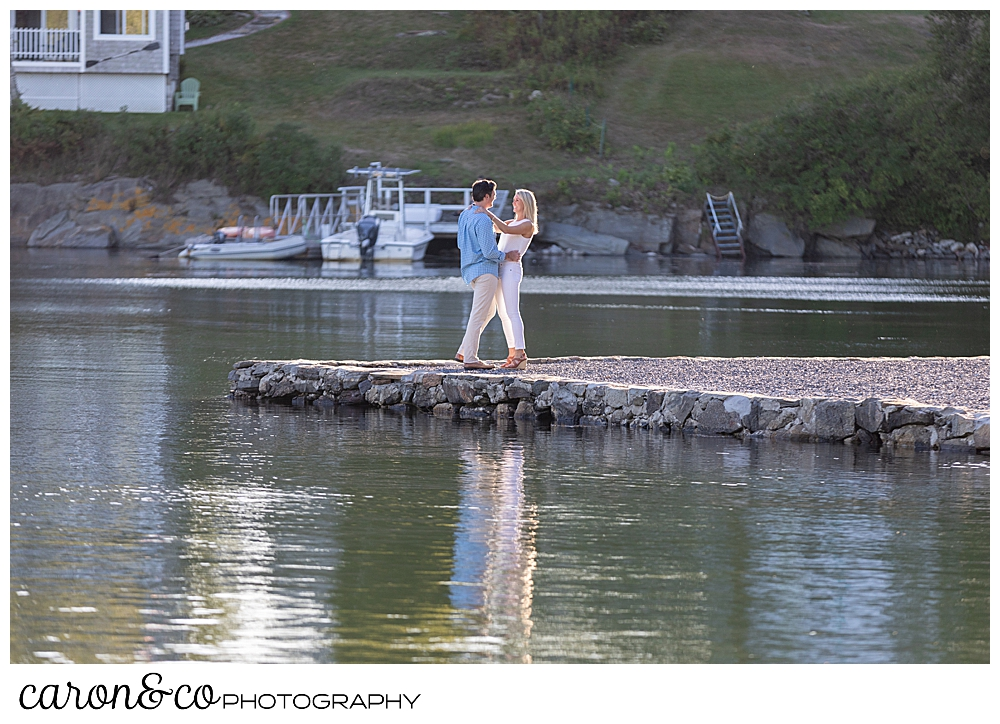a man and woman are standing face to face, at the water's edge during a Boothbay Harbor engagement session