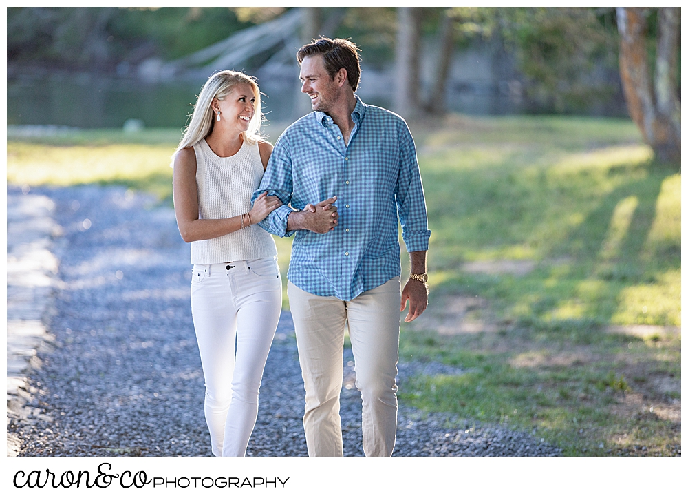 a woman wearing white, and a man wearing a blue shirt and tan pants, are walking arm in arm on the shore during a Boothbay Harbor engagement photo session