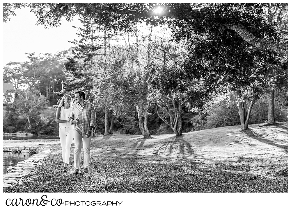 a black and white photo of a man and woman walking in a park along the water's edge, during a Boothbay harbor Maine engagement session