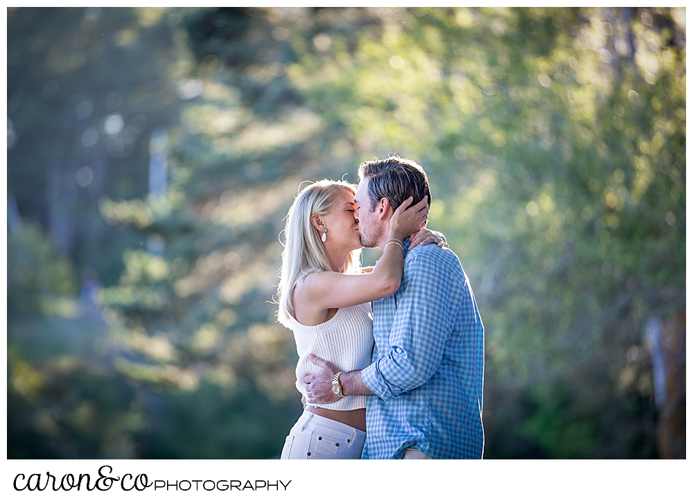 A woman in white and a man in blue and tan, are kissing in a park during a Boothbay Harbor engagement session in Maine