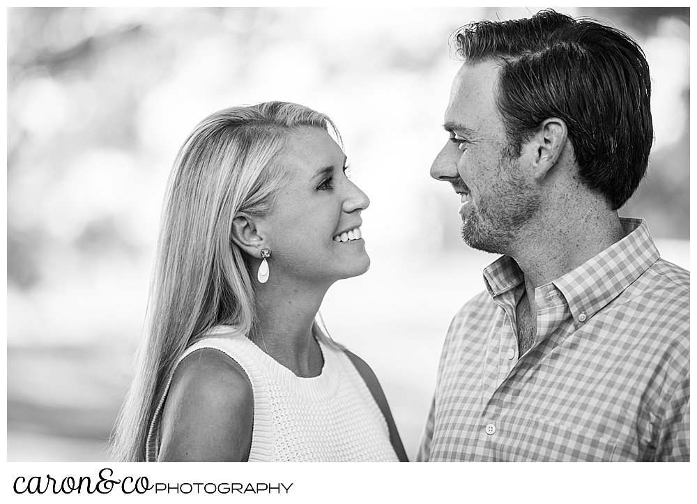 black and white photo of a man and woman standing face to face, smiling during their Boothbay Harbor engagement, Boothbay harbor, Maine