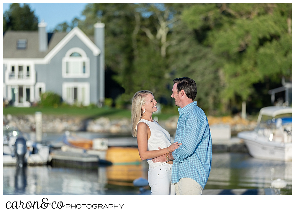 A woman in white, and a man wearing a blue shirt and tan pants, are standing face to face on a dock during their Boothbay Harbor engagement session in Boothbay Harbor, Maine