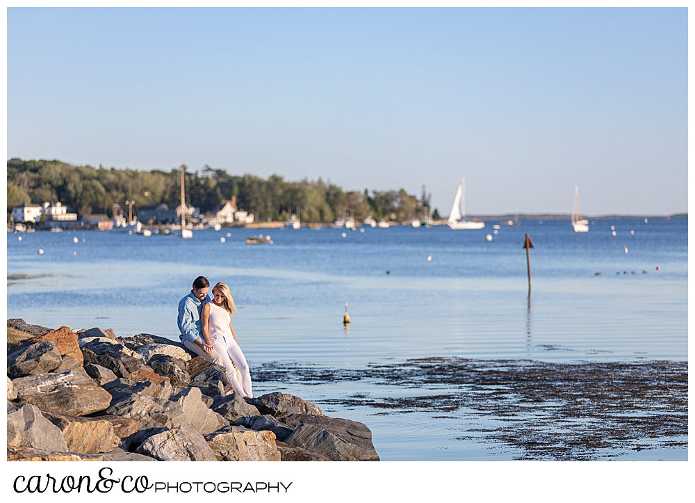A man and woman are sitting on the rock in Boothbay Harbor, Maine during a Boothbay Harbor engagement