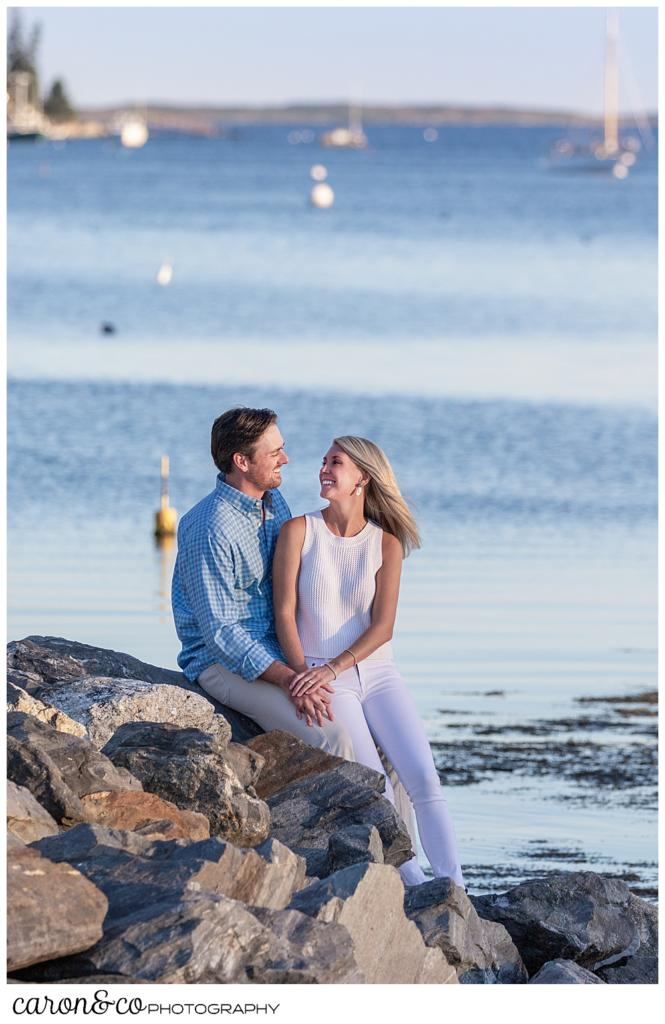 A woman and man are sitting on the rocks during a Boothbay Harbor, Maine engagment session