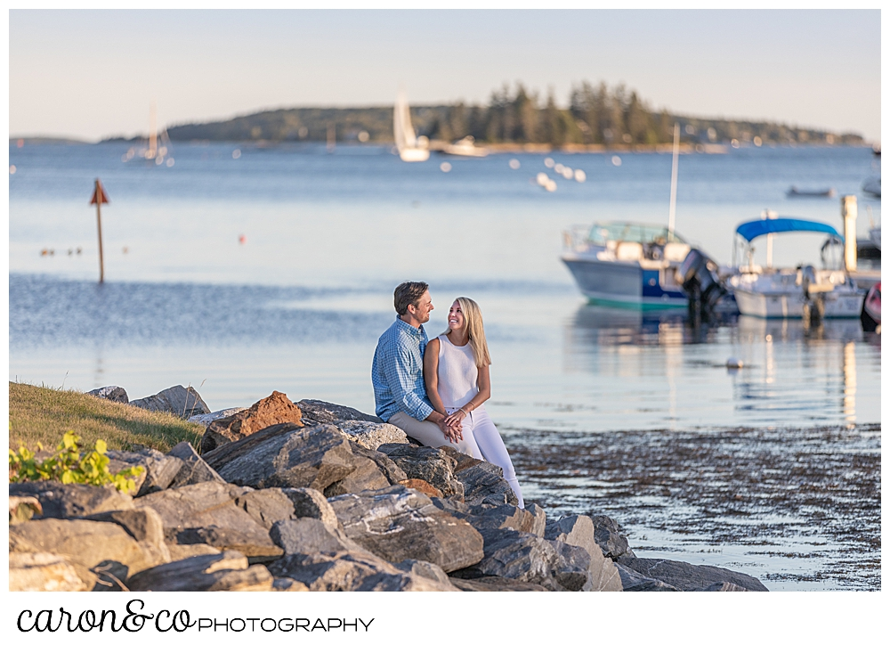 A woman and man sit together on the rocks with boats in the background of their Boothbay Harbor engagement photos