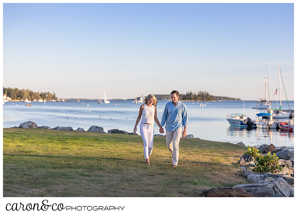 A woman in white, and a man in blue and tan, are walking hand in hand near Boothbay Harbor, during their Boothbay Harbor engagement photo session