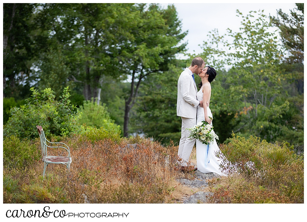 bride and groom kissing near a bench at Grey Havens Inn wedding, Georgetown Maine