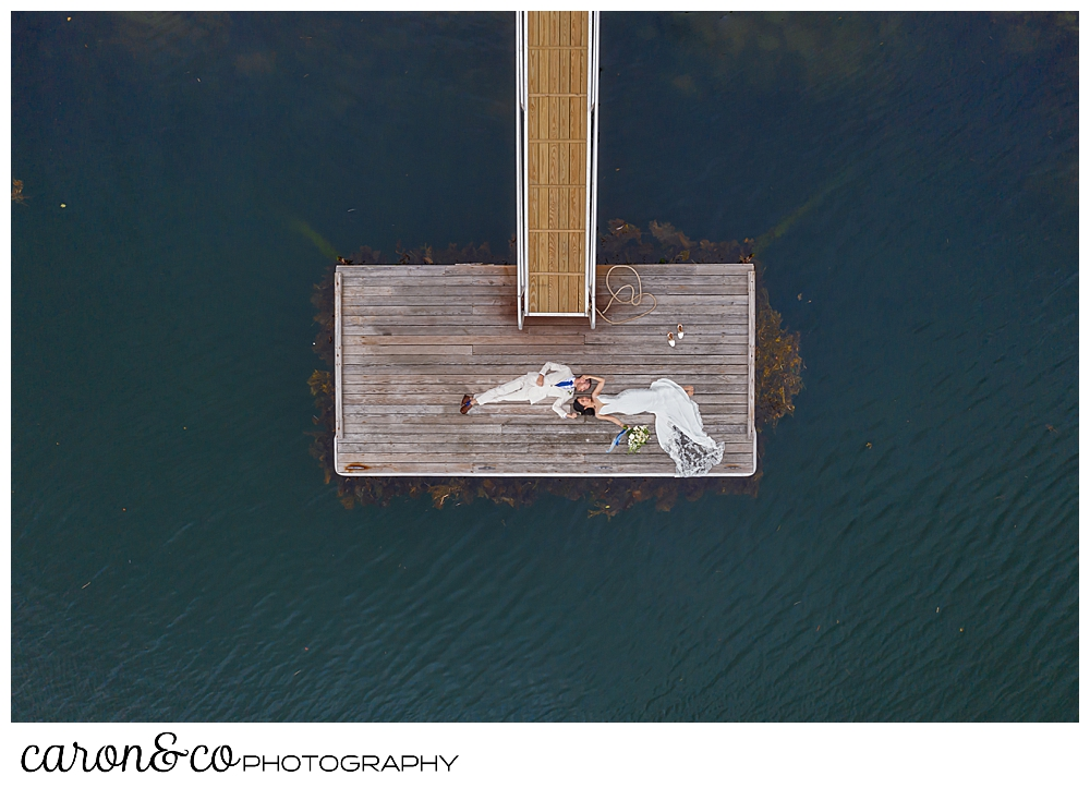 maine drone wedding photo of a bride and groom lying on a dock at a Grey Havens Inn wedding, Georgetown Maine