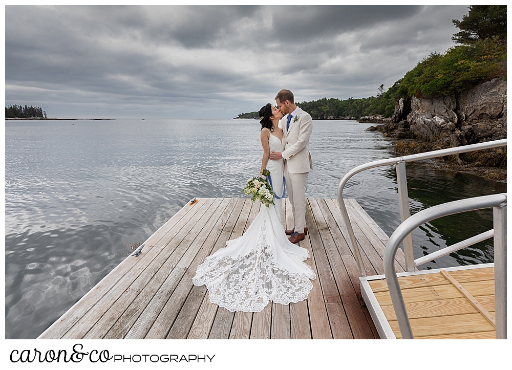 bride and groom kissing on a dock with a cloudy sky, at a Grey Havens Inn wedding, Georgetown Maine