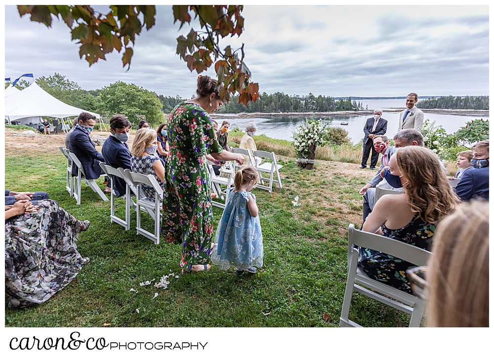 flower girl and her mother walk down the aisle of a Grey Havens Inn wedding ceremony, Georgetown Maine
