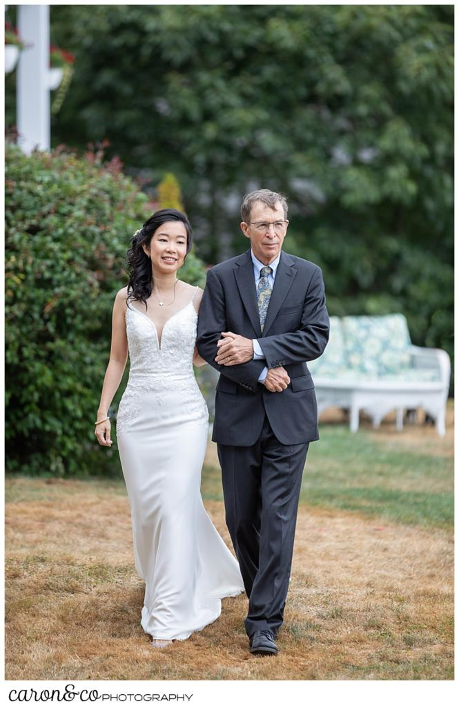 bride and her father-in-law-to-be, walk towards a Grey havens Inn wedding ceremony, Georgetown Maine