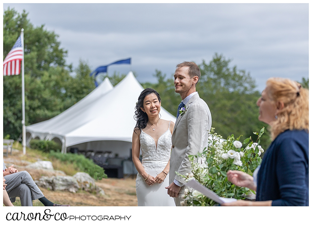 Bride and groom standing together during their Grey Havens Inn wedding ceremony, on the lawn in Georgetown Maine