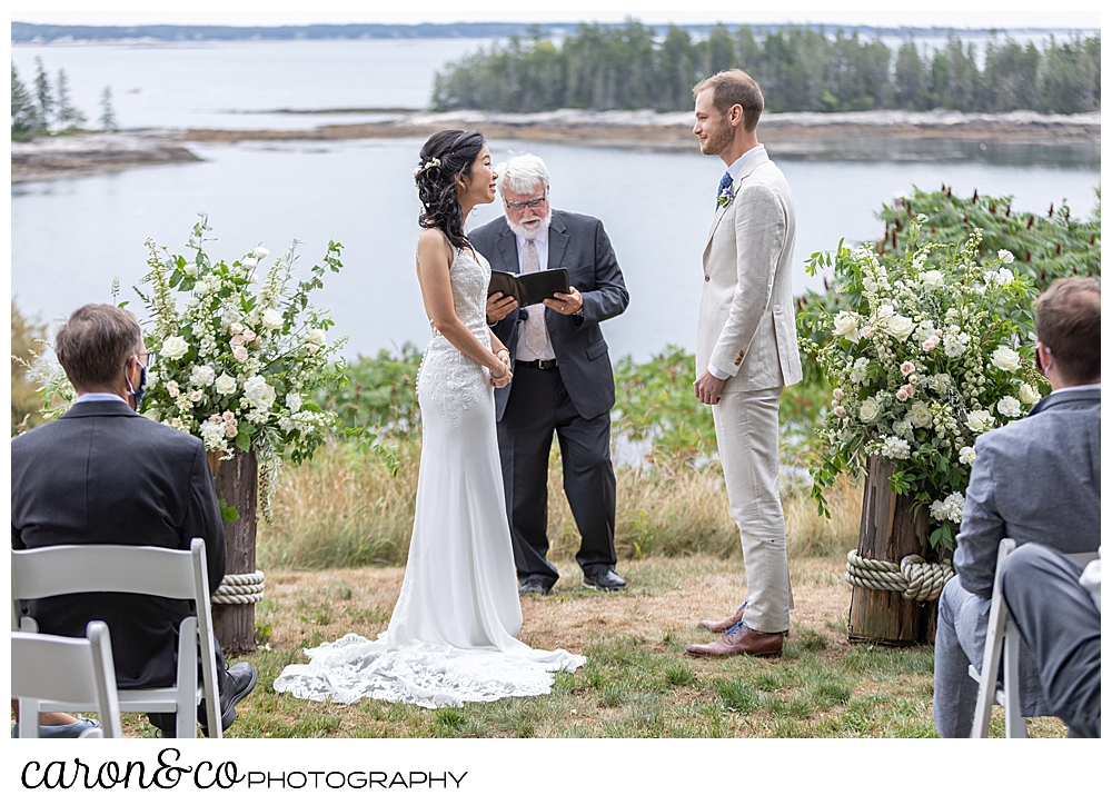 brideand groom stand in front of their officiant, on the lawn of their Grey Havens Inn wedding ceremony, Georgetown Maine