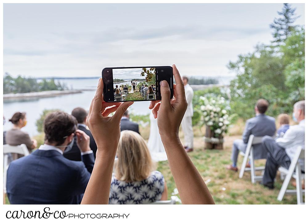 a guest takes a phone photo at a Grey Havens Inn wedding, Georgetown Maine