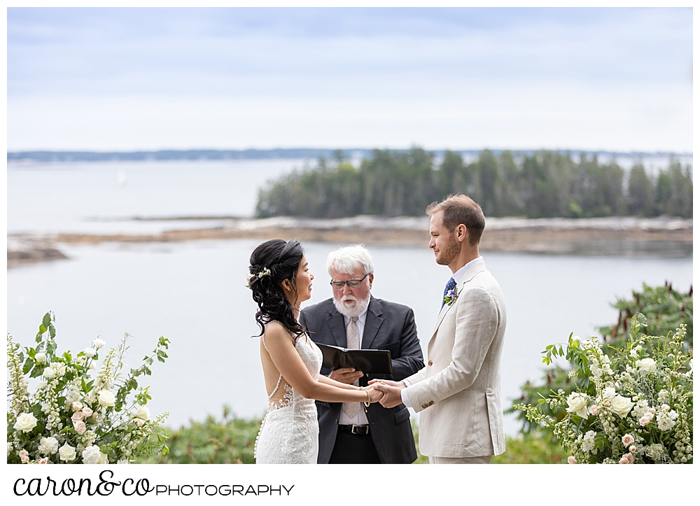 bride and groom holding hands in front of the officiant for their Grey Havens Inn wedding ceremony, Georgetown Maine