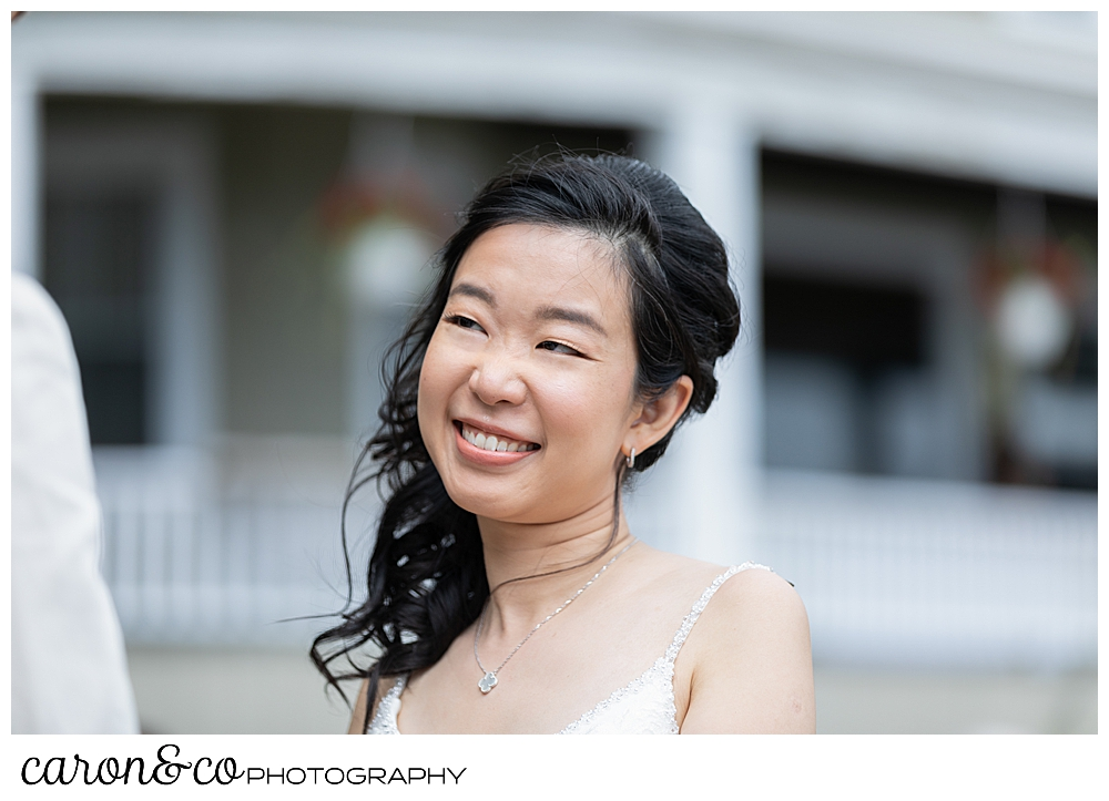 bride smiling during her Grey Havens Inn wedding ceremony on the lawn at Georgetown Maine