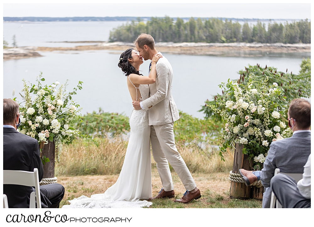 bride and grooms first kiss at their Grey Havens wedding ceremony on the lawn at Georgetown Maine