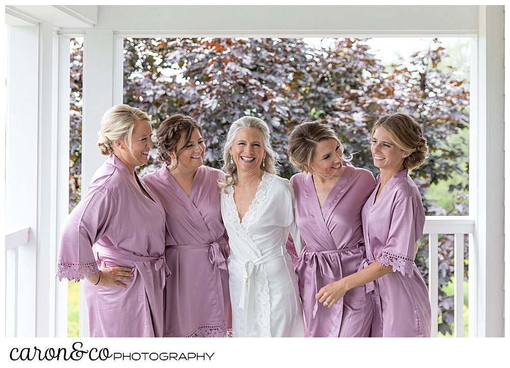 bride and bridesmaids in bathrobes, laughing during a Scarborough Maine wedding