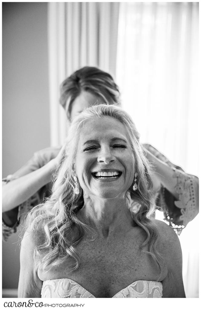 black and white photo of a bridesmaid helping a bride with her veil during a scarborough maine wedding