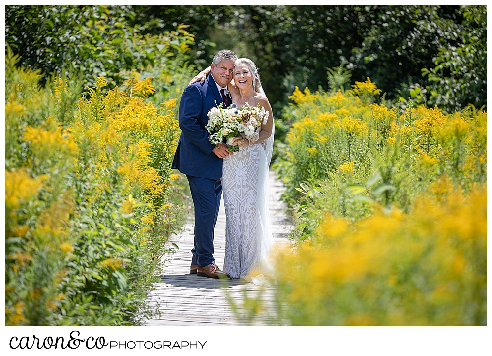 bride and groom posing on a boardwalk amid yellow flowers