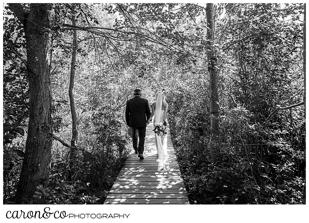 black and white photo of a bride and groom walking down a boardwalk in the woods