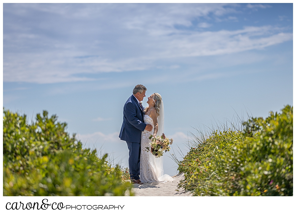bride and groom standing together on the beach, between the beach roses