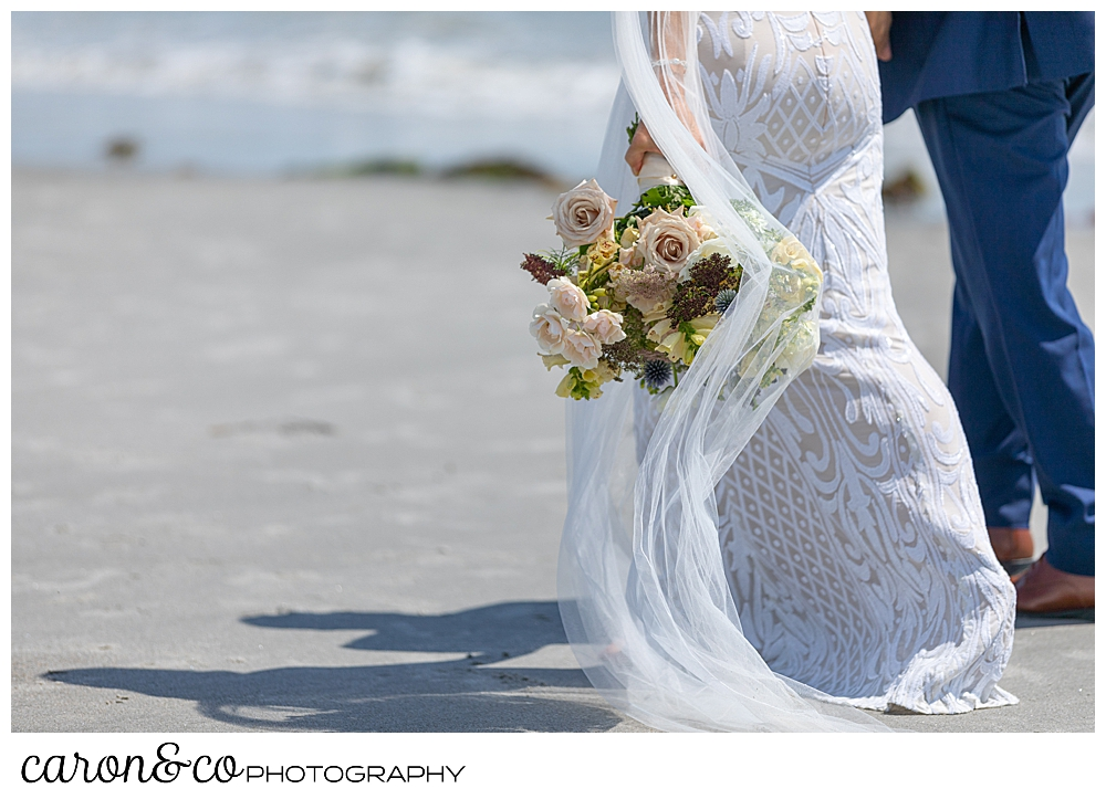 bride and groom walking along the water at the beach, the brides bouquet hangs down