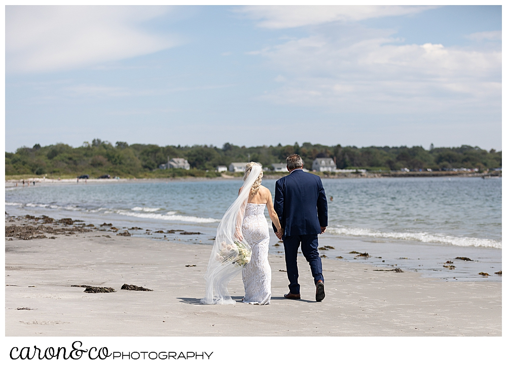 bride and groom, their backs to the camera, walk along the beach at the water's edge