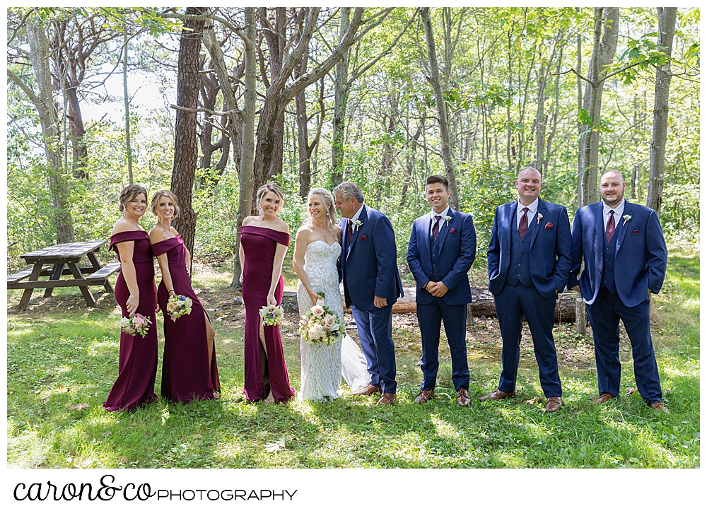bride and groom pose with their bridal party in the woods