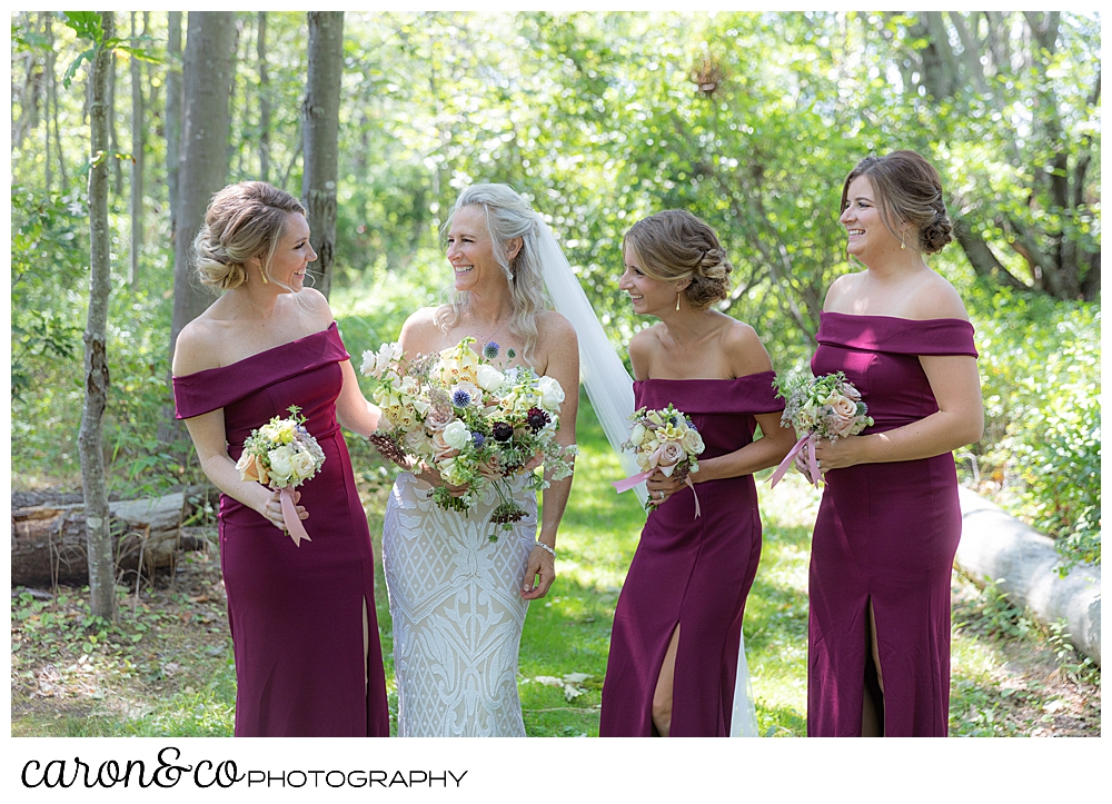 bride, and bridesmaids in dark red dresses, laugh together