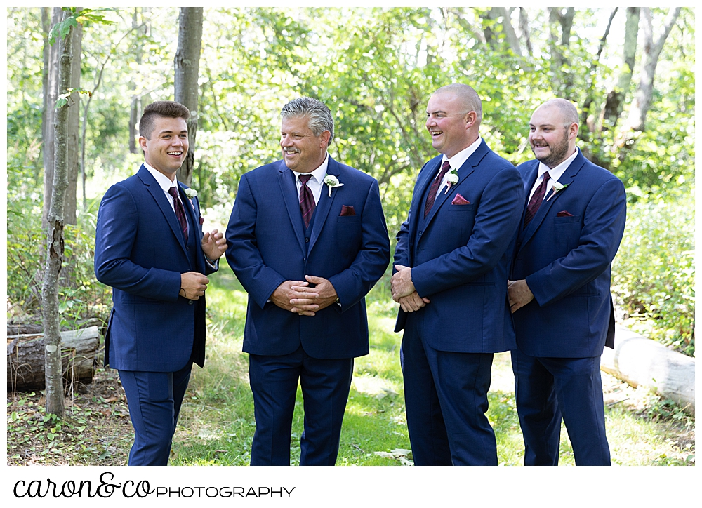 groom, and groomsmen in blue suits, stand together in the woods
