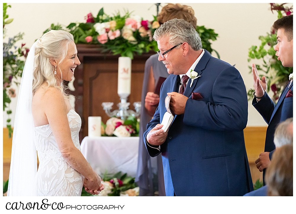 bride smiles at groom, as he takes his vows out during their spurwink church cape elizabeth maine wedding ceremony
